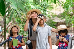 Asian family learning outdoor on vacation summer, mother and children walking on zoo or safari to new knowledge and writing, brother looking nature by telescope, sisters holding pen and notebook, Thai
