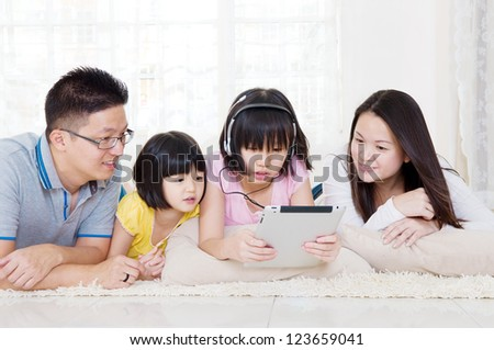 Asian family lying on floor using tablet computer