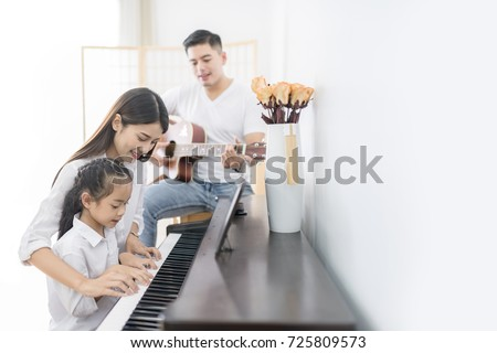 Asian family, mother  and daughter playing Piano,father playing guitar in family band at home, concept for family relationship