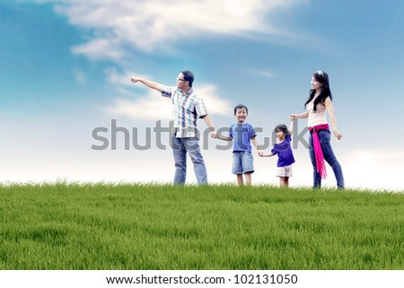Asian family of father, mother, and two kids  having a quality time in meadow. Shot at summer