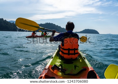 Asian family paddling on red and green kayaks in the sea.