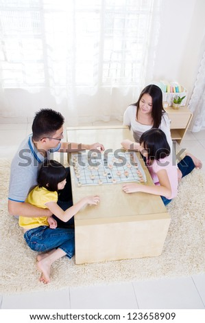 Asian family playing chinese chess