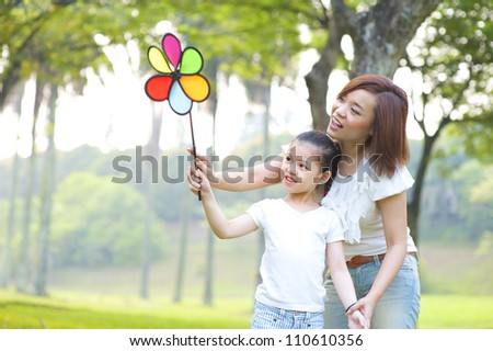 Asian family playing windmill at outdoor park