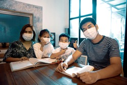 asian family quarantine at home reading book in home living room