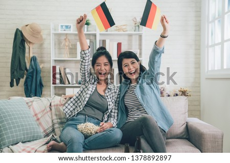asian family sisters cheering for German soccer team in front of TV at home. girls holding germany flag cheer up sitting on couch sofa raising arms hands. #1378892897
