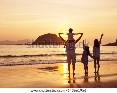 Shutterstock asian family standing on beach watching and enjoying the sunrise or sunset.
