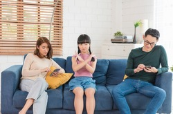 Asian family using tablet and mobile phones at home. addicted to devices, gadgets dependence overuse.