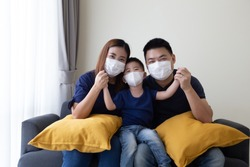 Asian family wearing protective medical mask for prevent virus Covid-19 and hand up and sitting together in living room. Family protection from contaminated air concept