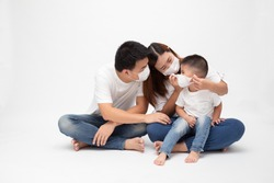 Asian family wearing protective medical mask for prevent virus Wuhan Covid-19 and sitting together on floor isolated white background. Family protection from contaminated air concept