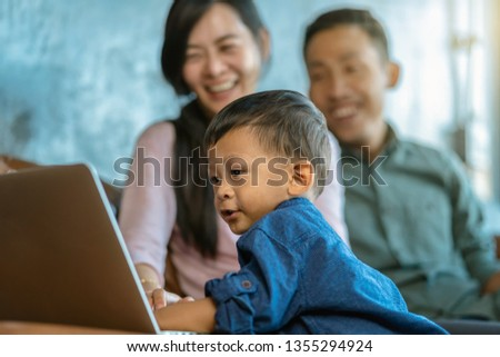 Asian family with son are looking the cartoon via technology laptop and playing together when living in loft house for Self learning or home school,Family home school concept
