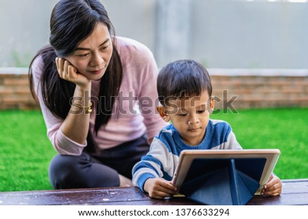 Asian family with son are looking the cartoon via technology tablet and playing together when living in front lawn for Self learning or home school,Family home school concept