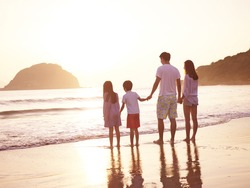 asian family with two children enjoying sunrise on beach.