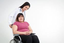 Asian fat woman sitting on a wheelchair Have a female doctor to help take care of inquiring about the illness. Obesity, health problem, weight loss concept. copy space