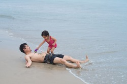Asian father and daughter are playing on the sand beach together with fully happiness moment, concept of learning by playing activity for kid and love in family lifestyle.