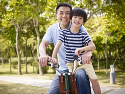 asian father and elementary-age son enjoying riding a bike outdoors in a park.