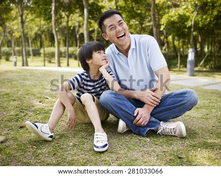 asian father and elementary-age son sitting on grass outdoors having an interesting conversation