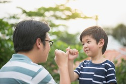 Asian father and his son making a pinkie promise on nature background