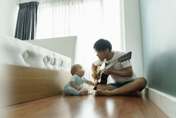 Asian Father and little Cute boy son sitting on wood floor singing and playing acoustic guitar together. Happy Family having fun on Vacation. Hobbies and Leisure Lifestyle at home.
