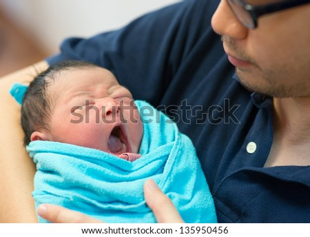 Asian father and newborn baby girl in hospital