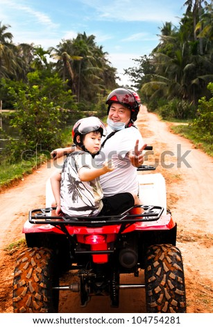 Asian Father and Son having a good time riding a quad bike.