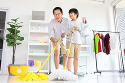 Asian father and  son help each other to clean the floor using mop and bucket for daily routine chores and housekeeping concept