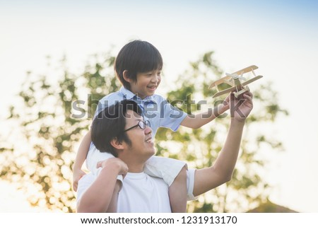 Asian father and son playing wooden airplane together in the park outdoors #1231913170