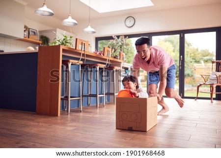 Asian Father And Son Pushing Son Around Kitchen Floor At Home In Junk Modelled Car