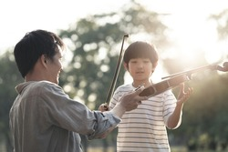 Asian father give and teach young boy kid to play violin in park together. Man educate music skill to his child to be specialist and professional in future. Nature outdoor violin class in evening.