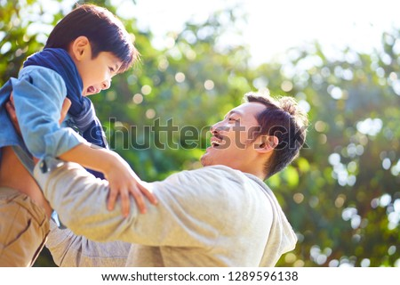 asian father having fun lifting son oudoors in park.