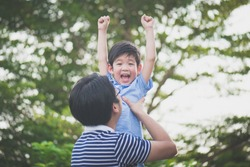 Asian father holding his son in the park