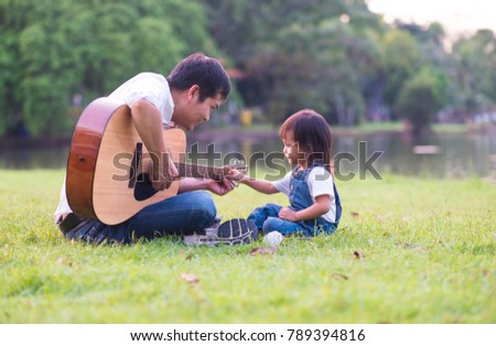 Asian father is playing guitar nearly with his daughter sitting and touching the guitar in the background of green park with happiness moment, concept of activity in family lifestyle. #789394816