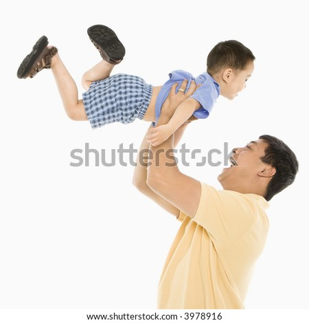 Asian father lifting son up into air in front of white background.