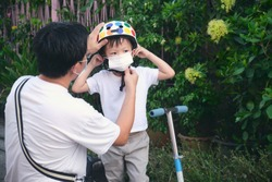 Asian father spending time with little son riding scooter in city, Parent putting mask on his toddler boy child during covid-19 outbreak, New normal lifestyle concept, Selective focus