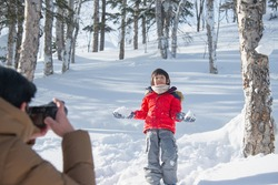 Asian father  taking photo of his little son during travel in winter