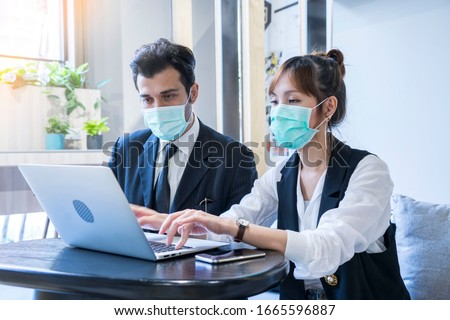 Asian female and Businessman workers meeting together with laptop and wear protective masks prevent PM 2.5 and corona virus or covid19 at co working space .Health and teamwork concept