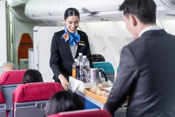 Asian female and male flight attendant serving food and drink to passengers on airplane. The cabin crew pushing the cart on aisle to serve the customer. Airline service job and occupation concept.