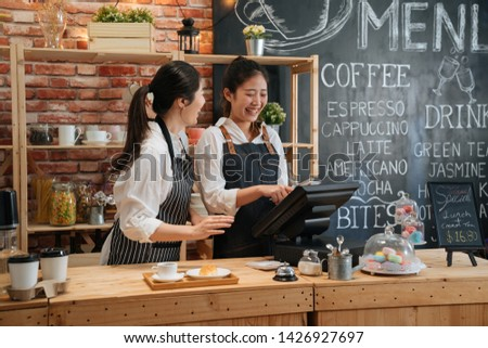 asian female barista telling something funny to colleague while working. two young girls coffeehouse staff laughing together and chatting gossip in modern coffee store. customer meal on bar counter