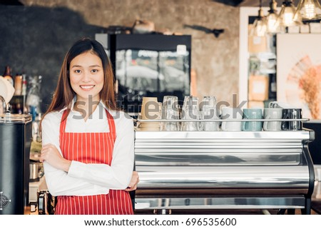 Asian female barista wear red apron crossed her arms at counter bar in front of coffee making machine with smile face,cafe service concept,owner business start up