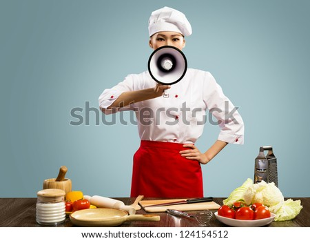 Asian female chef holds a megaphone, looking into the camera