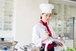 Asian female chef in kitchen. Cooking. Restaurant.