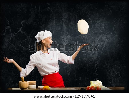 Asian female chef tosses a piece of dough, creative cooking