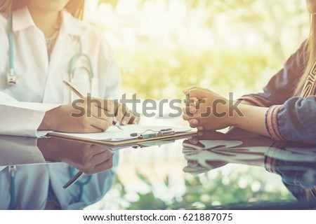 Asian female Doctor and patient are discussing something ,Having Consultation,Medical physician working in hospital writing a prescription, Healthcare and medically concept,selective focus
