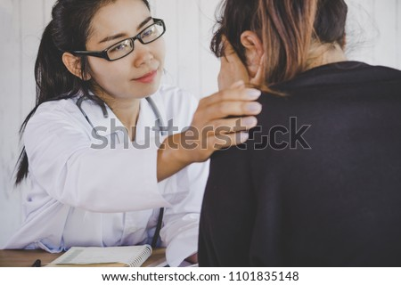 Asian female doctor comforting depressed patient at a hospital after the examination