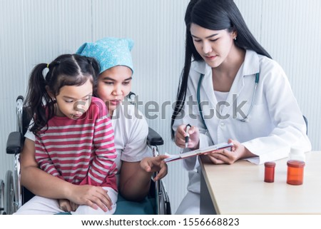 Asian female doctor Explaining treatment procedures And health insurance plans For women with cancer patients With a daughter sitting on his lab While the patient sits on the wheelchair #1556668823