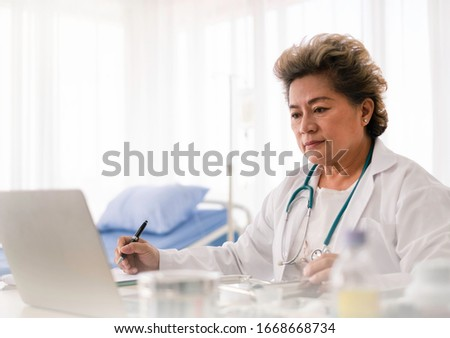 Asian female doctor using computer researching medical data for hospital treatment in hospital office. Asian  doctor using computer technology for paperwork after giving treatment. Doctor concept.