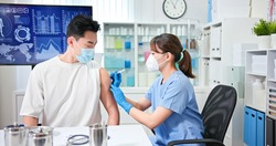 asian female doctor wearing face mask and gloves is making a vaccination in the shoulder of male patient in hospital