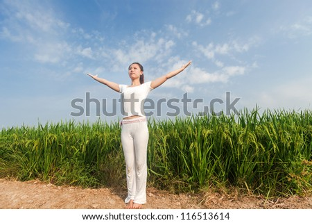 asian female doing yoga in the rice field