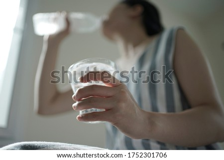 asian female drinking fresh mineral water for helping dehydration in summer season