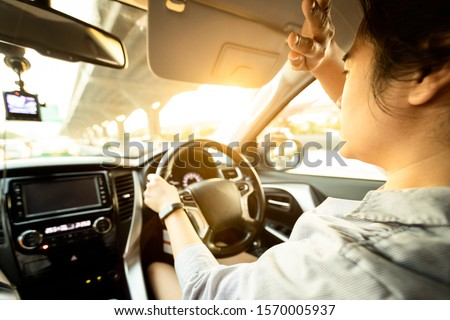 Asian female driver covering face by hand of bright sun,disturbed dazzled by sun light,difficulty in driving,young woman driving car feeling hot uncomfortable,risk of eye damage from ultraviole,UV ray Stock photo ©