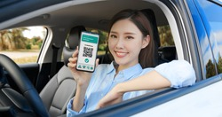 asian female driver shows health passport on mobile phone which indicates a vaccination against covid-19 in car